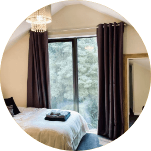 Interior of hills & ranges private bedroom with huge window & black curtains
