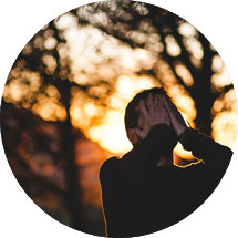 Circular image of man hiding his with hands standing in sunset forest
