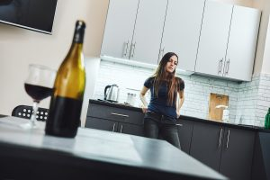 A young woman stands in her kitchen, and open bottle of wine and a full wine glass on the table. She looks distressed. Relapse, rehab, alcohol, addiction.