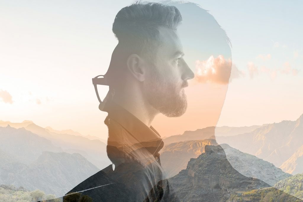 Triple exposure portrait of a man combined with beautiful mountain landscape at sunset