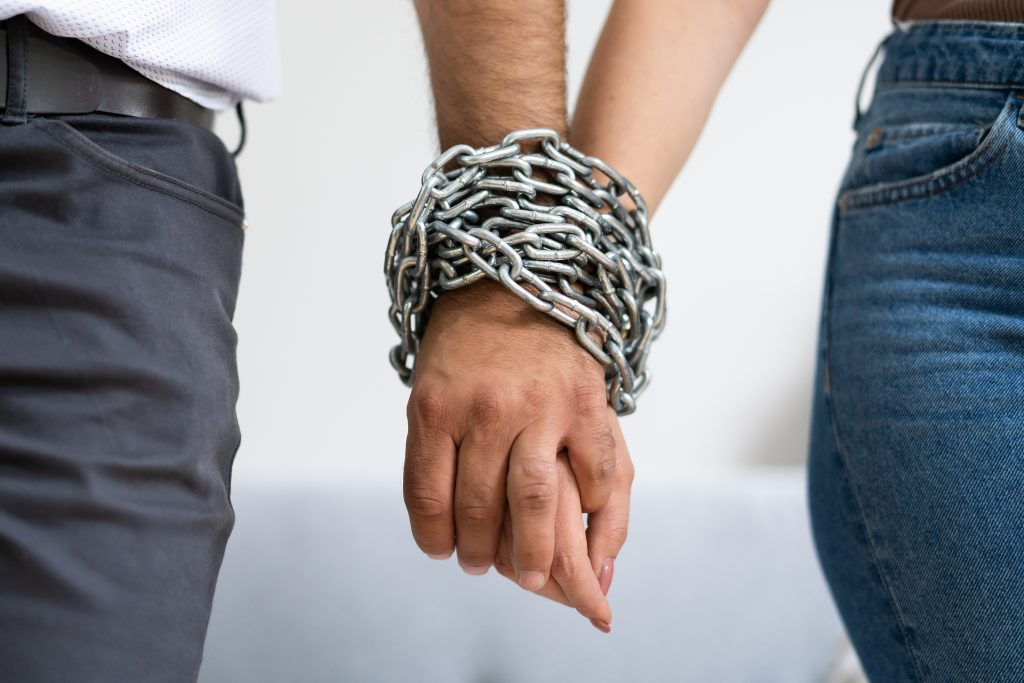Rear View Of Couple's Hand Tied With Metal Chain