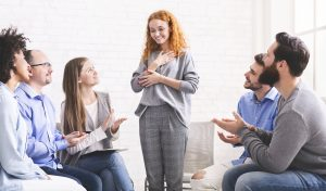 Free Of Addiction. Happy Woman Sharing Her Recovery Story With Group On Therapy Session In Rehab