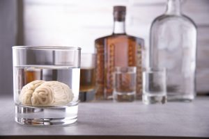 human brain in a glass with an alcoholic drink, against the background of bottles with alcohol. Alcohol addiction. Harm to the brain from alcohol