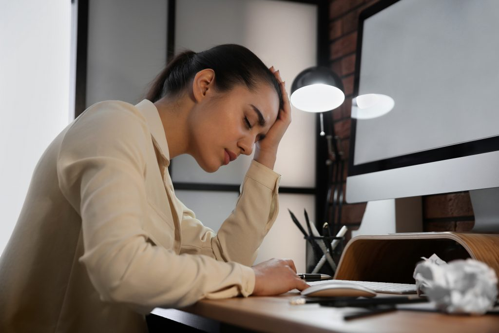tired stressed woman working on computer at night