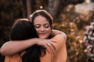 Two females hugging and supporting each other, practicing mindfulness